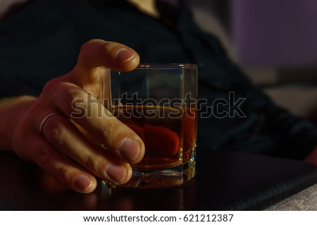 Yang man in black shirt with glass of whiskey