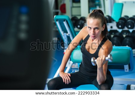 Yang pretty woman works out in gym. - stock photo