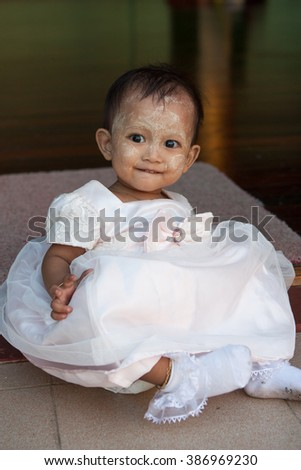 Yangon, Burma. November 26, 2011: Smiling little girl in a beautiful dress