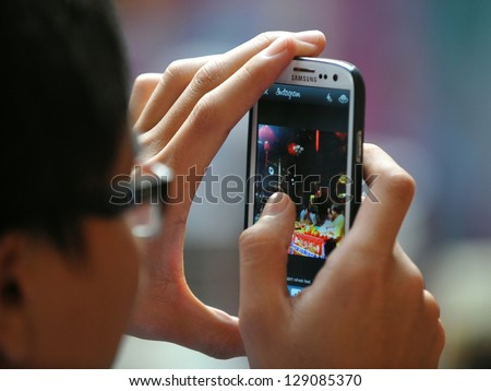 YANGON - FEB 10: A temple-goer uses a smartphone to share a photo via Instagram at a temple ceremony during festivities ushering in the Chinese new year of the snake on Feb 10, 2013 in Yangon, Burma. - stock photo