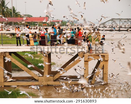 Yangon, Myanmar - February 24, 2011 : Burmese people feeding the hungry seagulls on the pier of Yangon at sunset