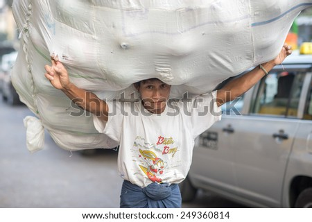 YANGON, MYANMAR - FEBRUARY 10: Burmese worker carries a huge load in Chinatown on February 10, 2014 in Yangon. Myanmar is ethnically diverse with 51 million inhabitants belonging to 135 ethnic groups. - stock photo