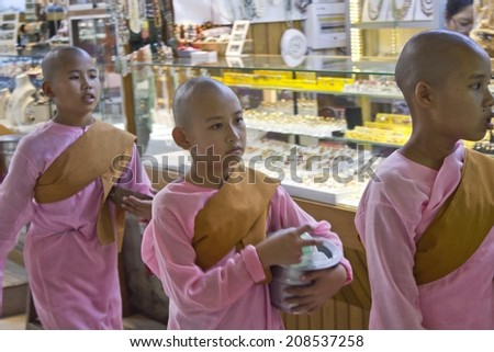 Yangon, Myanmar, February 27, 2014: Unidentified girl monks in a row asking charity at Yangon market - stock photo