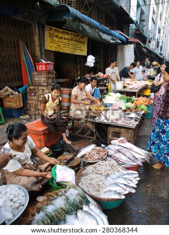 Yangon, Myanmar - February 24, 2011 : Young Burmese woman selling fresh seafood in the street market.