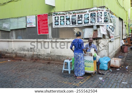YANGON, MYANMAR - JAN 14, 2015: Burmese people on street in Yangon, Myanmar. Yangon is the biggest city in Myanmar with population over 4 million people. - stock photo