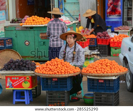Yangon, Myanmar - Jan 14, 2015. Burmese women selling fresh fruits at Bogyoke market in Yangon, Myanmar.