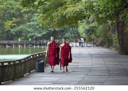 YANGON, MYANMAR - JANUARY 14, 2015: Unidentified monks walk around Kandawgyi Lake and Kandawgyi Nature Park in Yangon, Myanmar.  - stock photo