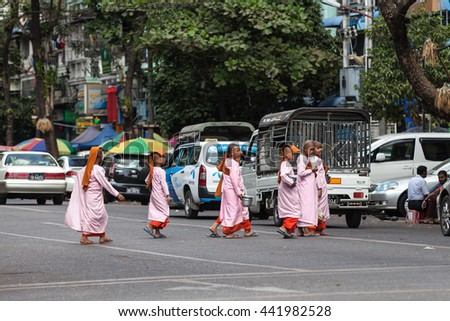 YANGON, MYANMAR - JANUARY 2, 2016:  Young buddhist nuns are crossing a street in Yangon, Myanmar on January 2, 2016 - stock photo