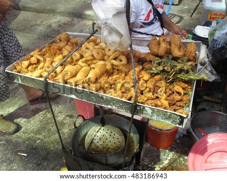 YANGON, MYANMAR - JULY 22, 2016 : Myanmar chef sell Fried snack, spring roll, seafood, vegetable in Chinatown market, Yangon, Myanmar