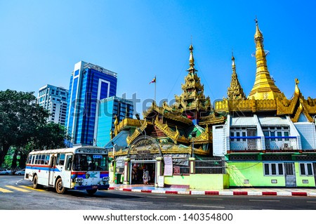 YANGON, MYANMAR - MAR 19, 2013: Traffic in downtown Yangon on Mar 19, 2013, in Yangon, Myanmar (or Burma).  In the middle of a roundabout, stands the Sule Pagoda, a religious and historic site. - stock photo