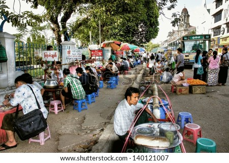 YANGON, MYANMAR - NOV.23; Unidentified people are eating by a foodstall on Nov.23, 2012 Myanmar.Foodstalls are a common site in Yangon were people are use to eat outside