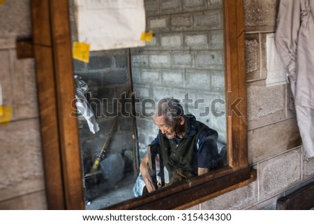 Yangon .  Myanmer 23 - February 2015 . The old man sitting in the barber shop.