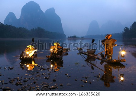 YANGSHUO, CHINA - OCTOBER 16: Chinese fishermans fishing with cormorants birds in Yangshuo, Guangxi region, traditional fishing use trained cormorants to fish, October 16, 2013 Yangshuo in Guangxi, China  - stock photo