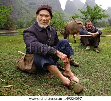 YANGSHUO COUNTY, GUANGXI, CHINA - MARCH 29: Elderly Chinese shepherds in green gumshoes, graze cattle near the Lijiang River, against the backdrop of karst hills, march 29, 2010. Guilin neighborhood.