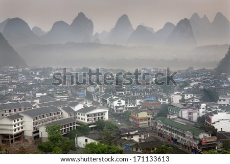 YANGSHUO TOWN , GUANGXI, CHINA - APRIL 1, 2010: Spring in South-west China, misty morning in the town of Yangshuo, small town surrounded karsts hills,  urban landscape, the top view.