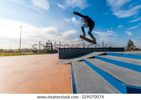 Yanino-1, Russia, October 17 2015: Openning new skatepark near Saint-Petersburg. Young man doing trick on the kick scooter in the park.