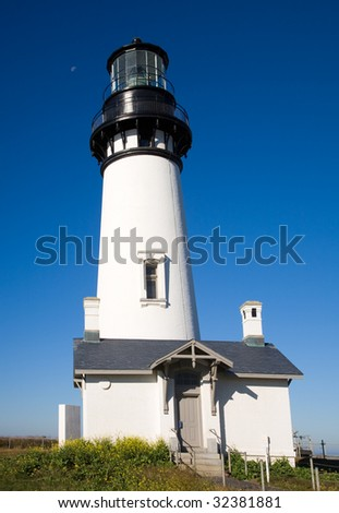 Yaquina Head Lighthouse, with a cloudless blue sky.