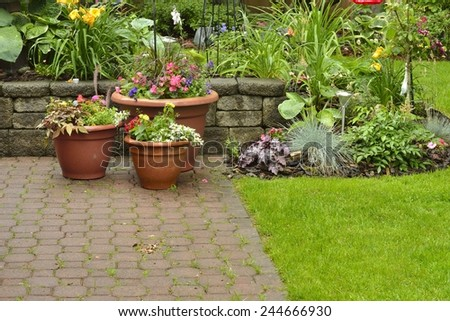 Yard and Patio. Beautiful yard and patio with flower pots and garden mixed with perennials and annuals. - stock photo