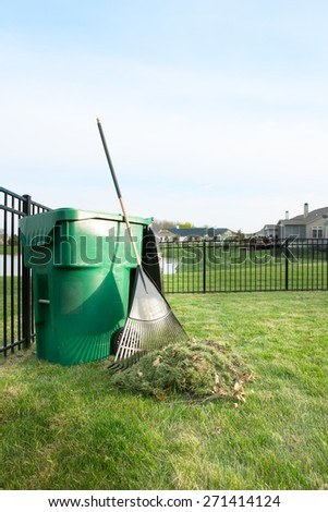 Yard maintenance in spring cleaning the lawn and raking up grass clippings after mowing with a pile of grass and rake leaning on a plastic bin for composting - stock photo