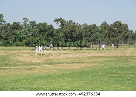 Yard signs in driving range and golf ball at day time. A horizontal shot of driving range showing yardage signs for 100, 125, 150 feet target on green natural grass meadow in Houston, Texas, US.