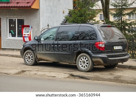 YAREMCHE, UKRAINE - JANUARY 16, 2016: Black dirty Chrysler Caravan at the roadside. Chrysler Caravan is the european version of Dodge Caravan. - stock photo