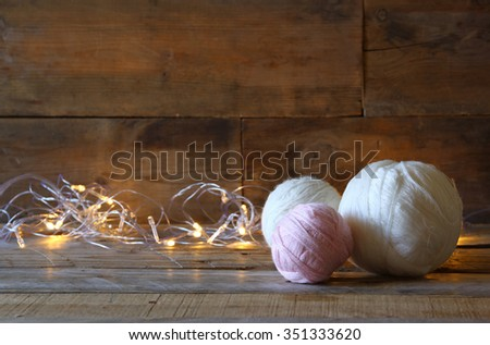yarn balls of wool on wooden table with garland gold lights  - stock photo