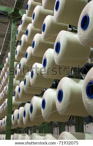 Yarn cone mounted in a fabrics factory. - stock photo