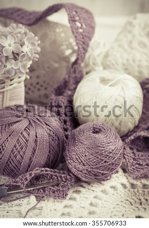 Yarn for crochet and knitted openwork napkins, still life photo with tools for handmade. For this photo applied toning in retro style.