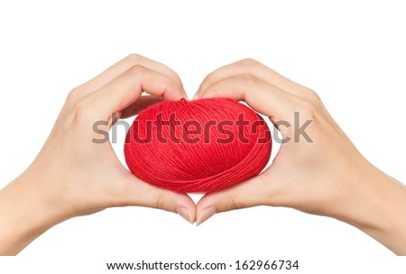 Yarn red threads for knitting in a woman hands isolated on white background cutout - stock photo