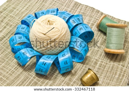 yarn, thimble and spools of thread on fabric - stock photo