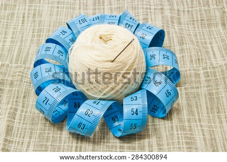 yarn with needle and meter on fabric - stock photo