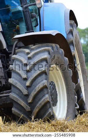 YARNFIELD, STAFFORDSHIRE, ENGLAND - 6TH SEPTEMBER 2014: A close up of a stationary blue tractor's large tires. - stock photo