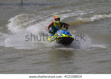 Yasothon Thailand - July,02, 2016: Young Man on Jet Ski. Professional jet ski rider. Jet Ski Championship. Jetski performs many tricks on the waves.