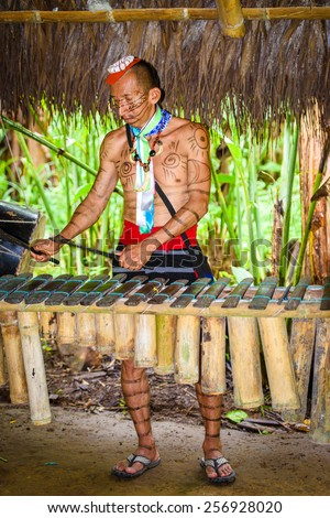 YASUNI, ECUADOR - JAN 4, 2015:  Unidentified Ecuadorian indian makes music. Indigenous indians  are protected by COICA (Coordinator of Indigenous Organizations of the Amazon River Basin) - stock photo