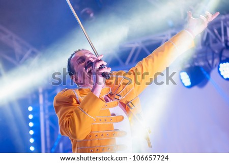 YATELEY, UK - JUNE 30: Professional Freddie Mercury tribute artist Steve Littlewood in the spotlight while performing at the GOTG Festival in Yateley, UK on June 30, 2012 - stock photo