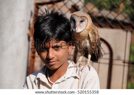 YAVATMAL, MAHARASHTRA, INDIA : unidentified young boy with Barn owl sitting on his shoulder.