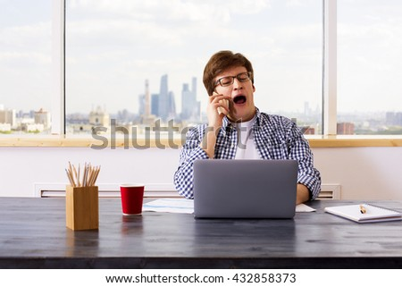 Yawning european man having mobile phone conversation at office desk with laptop, business report, coffee cup and stationery items. Front view