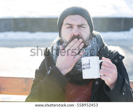 yawning man, bearded hipster with beard and moustache covered with white frost drinks from cup with good morning text sitting on wooden bench on snowy winter day outdoors on natural background