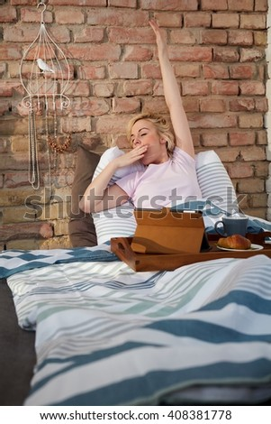 Yawning, stretching woman waking up in the morning in bed. - stock photo