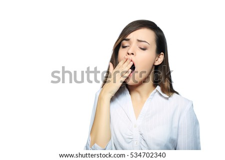 Yawning tired woman. Beautiful caucasian model isolated on white background.