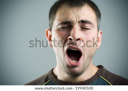 Yawning young man. - stock photo