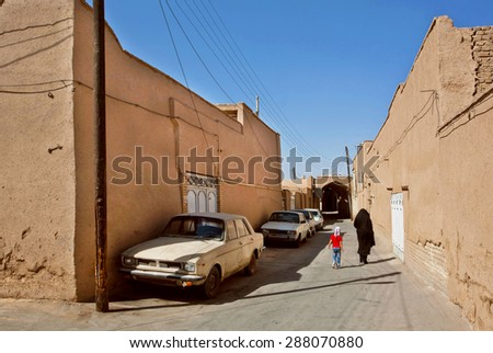 YAZD, IRAN - OCT 20: Iranian family walking past the clay houses and retro cars in deserted city on October 20, 2014. With population of 270.600 families, Yazd is the centre of Persian architecture - stock photo