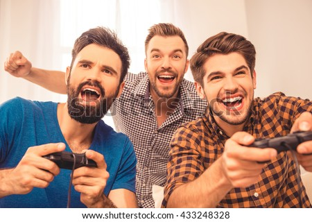 Yeah! close up photo of excited happy cheerful men play video game - stock photo