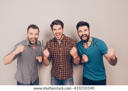 YEAH! three  handsome screaming men showing their strong hands - stock photo