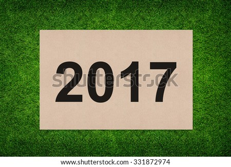 Year 2017 - Alphabet number on brown paper texture with green grass background.