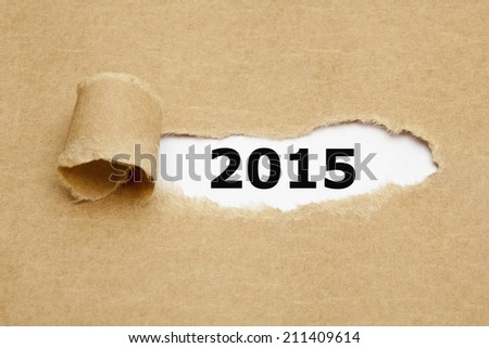 Year 2015 appearing behind torn brown paper. - stock photo