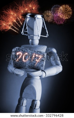 Year 2017, manikin mannequin human artist drawing model holding a wine cork on black background with fireworks.