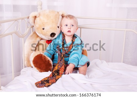 year-old child portrait in men's tie and toy bear in home interior