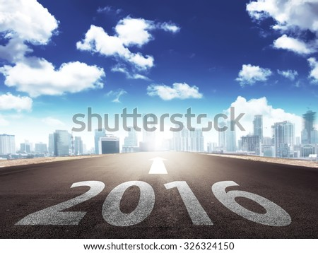 Year 2016 on the street with arrow toward to the city - stock photo