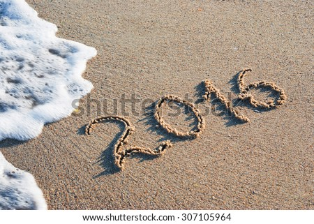 Year 2016 written in sand on a sea beach. - stock photo